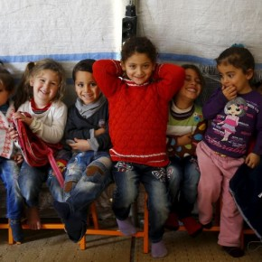 Syrian refugee girl Ele Cundi, 5, poses as she sits with her friends in a kindergarten at Midyat refugee camp in Mardin province, Turkey, December 14, 2015. Syria's conflict has left hundreds of thousands dead, pushed millions more into exile, and had a profound effect on children who lost their homes or got caught up in the bloodletting. The drawings of young refugees living in Turkey show their memories of home and hopes for its future. The pictures also point to the mental scars borne by 2.3 million Syrian refugees living in Turkey, more than half of them children. REUTERS/Umit Bektas