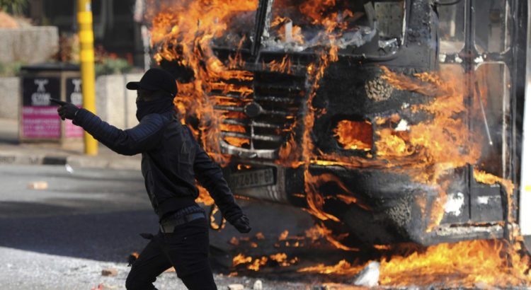 A protesting student runs past a burning bus off campus outside the University of the Witwatersrand on Monday, Oct. 10, 2016 in Johannesburg, South Africa. Tear gas and water cannon were fired as hundreds of students protested at the university amid a bitter national dispute with university managers and the government over demonstrators' demands for free education, forcing student into the neighbouring city streets.  (AP Photo)