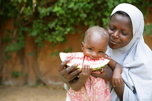 28 September 2010, a mother holds her child while eating a slice of watermelon in Niamey the capital of Niger. In Niger many common childhood killer diseases such as diarrhoea, acute respiratory infections and malaria can be prevented with increased knowledge and adoption of key family practices such as exclusive breastfeeding up to six months, birth spacing, proper use of oral rehydration therapy and complementary food and regular hand washing among others. UNICEF and its partners work at the institutional, community, household and health facilities levels to promote the adoption of key family practices through community-driven initiatives and via the combination of traditional and modern communication channels to raise awareness on the links between poor hygiene, water and sanitation and the spread  of diseases in populations.