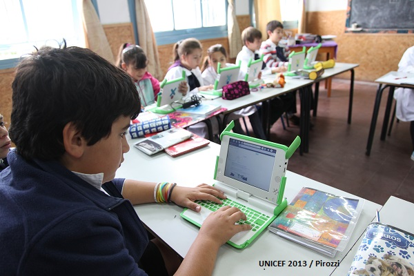 (Foreground) Alfonso, 11, uses a special laptop issued through the Plan Ceibal initiative, at the rural public school in the city of Las Brujas, in the south-central Canelones Department. Other children, also using laptops, are seated nearby. Plan Ceibal aims to promote digital inclusion in order to reduce the digital divide, both with respect to other countries and between the citizens of Uruguay, in order to enable greater and better access to education and culture. Promoting equal opportunities for all pupils in primary education by providing a laptop to every child and teacher are among the plan's objectives.
