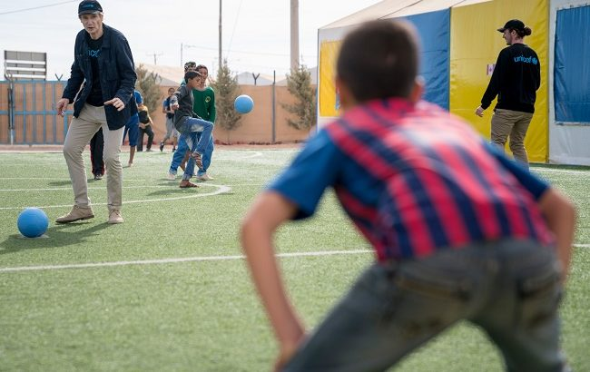 """UNICEF Goodwill Ambassador Liam Neeson plays football during a visit to a Makani centre in Za'atari refugee camp in Jordan on Nov 7, 2016. Makani ('My Space' in Arabic) provides 3 key services for children under one roof: learning support, life skills training and psychosocial support services.   This centre has been particularly effective in using sports like football, wrestling and Zumba to help adolescent boys and girls cope with their stress.  Makani centres in host communities are open to all children in the community. A majority of children are Syrians, but there are also Jordanian, Iraqi and children of other nationalities in many of the centres.     About 14 km from the Syrian border, Za'atari is the largest Syrian refugee camp in Jordan with a population of 79,000. Established in July 2012, the camp hosted as many as 130,000 refugees at the peak of the refugee influx in mid-2013.    On 8 and 9 November 2016 in Jordan, UNICEF Goodwill Ambassador Liam Neeson and his eldest son Micheal met with Syrian children, young people and their families whose lives have been greatly affected by the conflict in Syria - now close to its sixth year.  """"Every person has a story of loss and of witnessing horrific violence that no one – least of all a child - should ever have to see,"""" said Neeson after visiting the Za'atari refugee camp near the Syrian border on Monday. """"I truly admire the strength and spark of the children I met, the girls in particular. They want to be doctors, lawyers, police officers and engineers so that when they can go back to Syria they can rebuild their country. It is incredibly inspiring to see how education so empowers them. I will never forget them."""""""